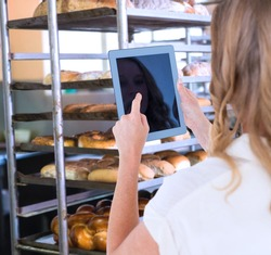 Woman using tablet pc against catering building with shelf of hot breads