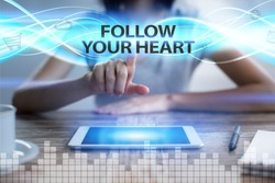 Woman using tablet pc, pressing on virtual screen and selecting follow your heart.