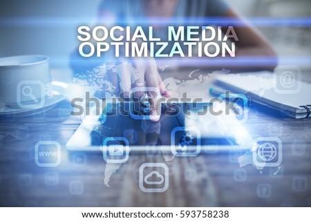 Woman using tablet pc, pressing on virtual screen and selecting social media optimization.
