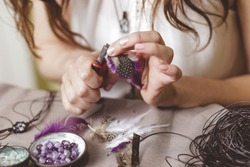Woman using tools for making gemstone jewellery, home workshop. Women artisan created jewellery. Art, hobby, handcrafted concept