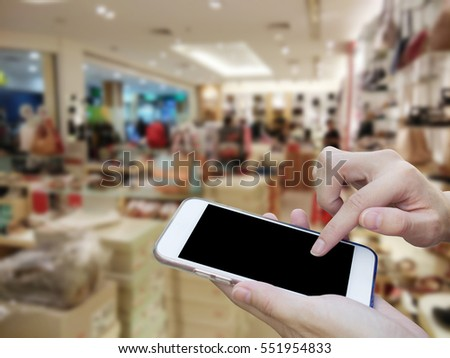 Woman using touch screen mobile phone with blur shopping mall #551954833