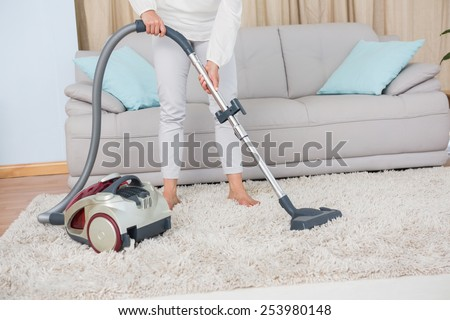 Woman using vacuum cleaner on rug at home in the living room