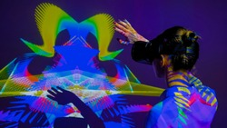 Woman using VR headset and waving hands in front of large wall display with augmented reality mirror effect at modern futuristic immersive exhibition or museum. AR, future, art, technology concept