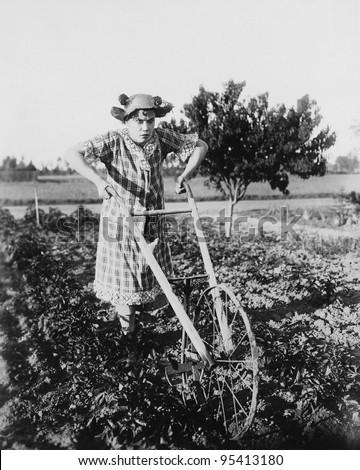 Woman using walking plow in garden