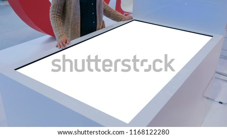 Woman using white blank touchscreen display terminal at modern technology show. Mock up and technology concept