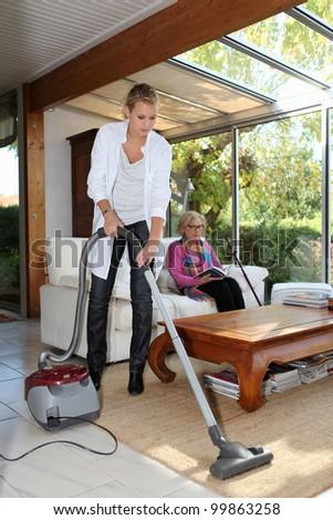 Woman vacuuming in senior woman\'s house