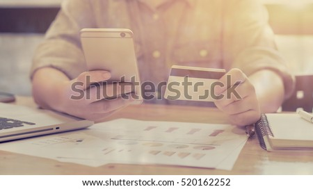 Woman verifies account balance on smartphone with mobile banking application.Online payment,Women\'s hands holding a credit card and using smart phone for online shopping,selective focus,vintage color