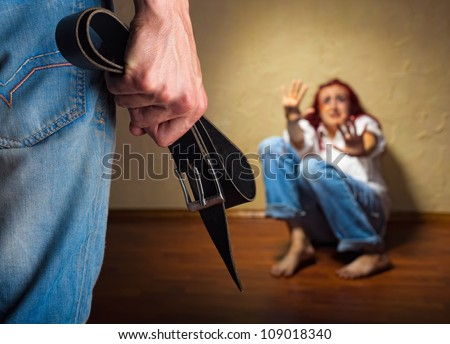 Woman victim of domestic violence and abuse. Husband intimidates his wife. Focus on the arm with a belt - stock photo
