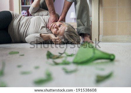 Woman victim of domestic violence and abuse. Mature woman scared of a man with broken bottle