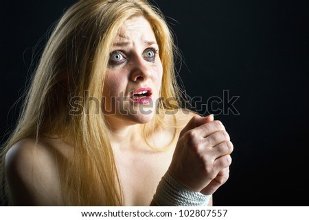 Woman victim of domestic violence and abuse on dark background