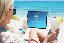 Woman viewing weather forecast on tablet while relaxing on the beach
