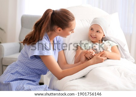 Woman visiting her daughter who is undergoing course of chemotherapy in clinic. Childhood cancer awareness concept