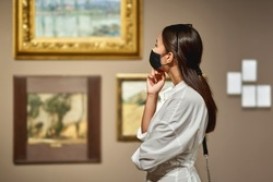 woman visitor wearing an antivirus mask in the historical museum looking at pictures