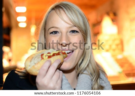 Woman visits Christmas market or fair at night and eats Hot Dog as a snack #1176054106