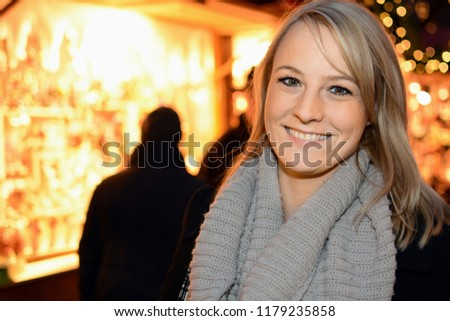 Woman visits Christmas market with many stalls for Advent and winter #1179235858