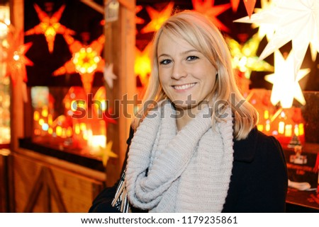 Woman visits Christmas market with many stalls for Advent and winter #1179235861