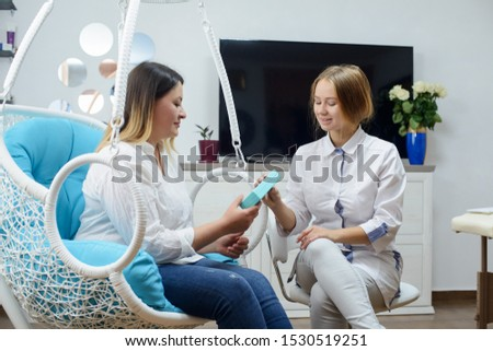 Woman visits young cosmetologist doctor. The doctor consults with the patient #1530519251