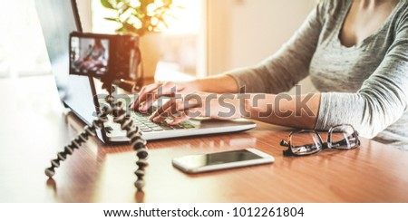 Woman vlogger using laptop computer while making video feed vlog - Girl sharing her content online for vlog at home - New digital job trends and technology concept - Focus on left female hand