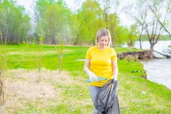 Woman volunteer scavenges garbage in the summer park. Volunteer and ecology concept. Empty space for text