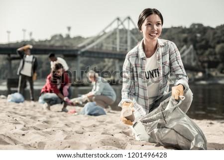 Woman volunteering. Beautiful dark-haired woman wearing squared shirt enjoying the process of volunteering cleaning the beach