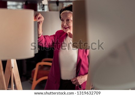 Woman waist-shot. Waist shot of beautiful elegant aging fancy worn female with radiant smile in store #1319632709
