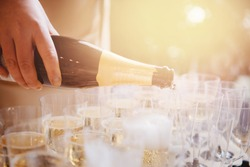 Woman waiter spills champagne from bottle into glasses. caterer banquet