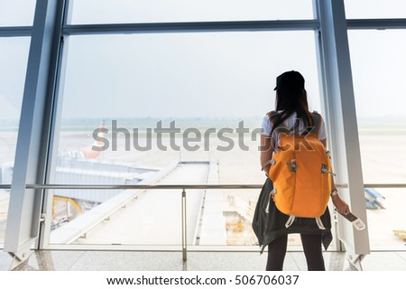 Woman waiting for a flight at the airport; window airport.