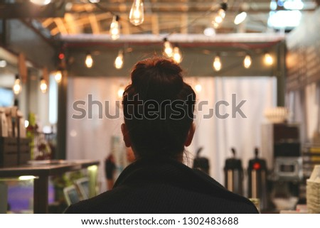 Woman waiting for her coffee at a cafe with string lights  #1302483688