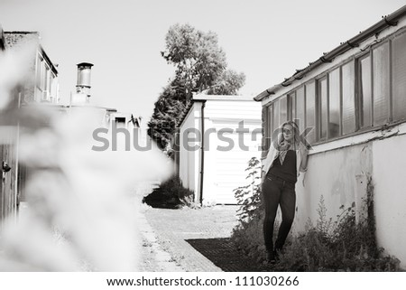 woman waiting for someone standing by a wall down a side street