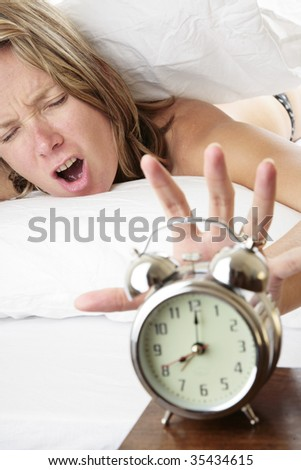 Woman waking up late and reaching for her alarm clock