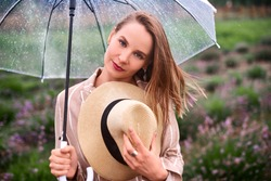 woman walk in blooming fields holding umbrella and straw hat. shallow depth of field photo