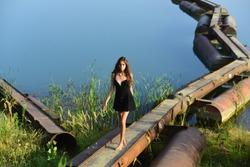 Woman walk on metal pontoon bridge over river. Girl in summer dress barefoot on iron construction on blue water. Summer vacation concept. Adventure, discovery, traveling, wanderlust.