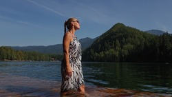 Woman walk on water on pier in sunglasses and a boho silk shawl. Girl rest on a flood wood underwater dock. The pavement is covered with water in the lake. In the background are mountain and a forest.