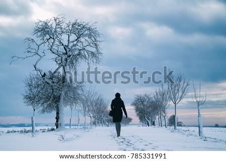 Stock Photo woman walking alone in winter landscape in moody weather, hiking girl in snowy landscape with dark skyline