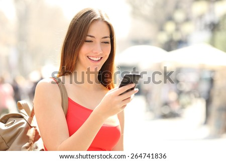 Woman walking and using a smart phone in the street in a sunny summer day #264741836