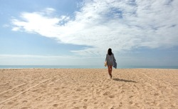 Woman walking away in the distance across a sandy tropical beach to the sea on a sunny spring or summer day with copy space in a vacation or travel concept