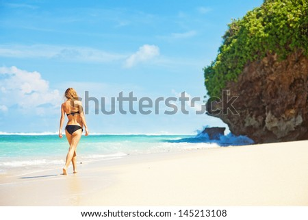 woman walking away on the idylic beach