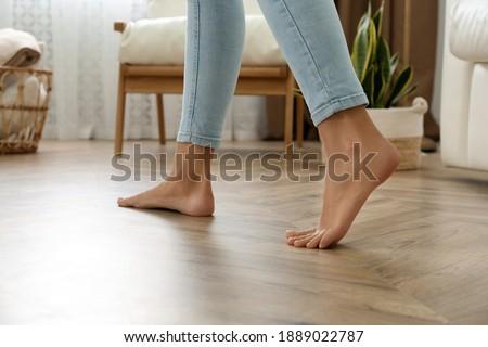 Woman walking barefoot at home, closeup. Floor heating concept