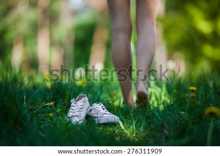 Woman walking barefoot on the green grass, shoes in focus, shallow DOF ストックフォト ©