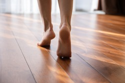 Woman walking barefoot on toes at warm laminate floor close up rear view. Sunny light bedroom good morning welcome new day, modern comfy apartments with under floor heating system, footcare concept