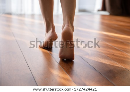 Woman walking barefoot on toes at warm laminate floor close up rear view. Sunny light bedroom good morning welcome new day, modern comfy apartments with under floor heating system, footcare concept Foto stock ©