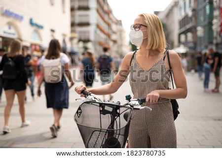 Woman walking by her bicycle on pedestrian city street wearing medical face mask in public to prevent spreading of corona virus. New normal during covid epidemic. Social responsibility. Photo stock ©