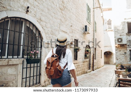 woman walking by tight streets of kotor, montenegro
