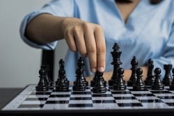 Woman walking chess pieces on a chessboard. Black chess pieces. Compare a chessboard to running a business. Concept of business administration.