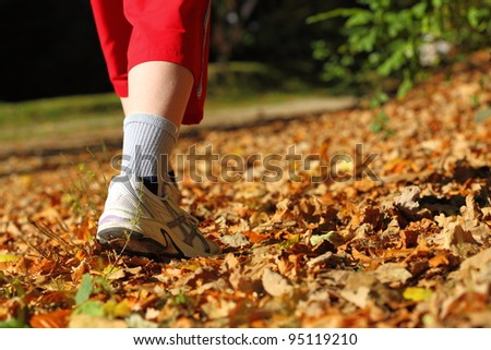 Woman walking cross country and trail in autumn forest