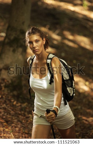 Woman walking cross country in autumn forest