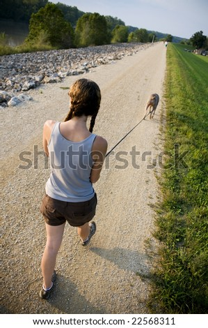 woman walking dog on trail