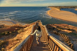 Woman walking down iconic Port Noarlunga boardwalk while watching spectacular sunset view, South Australia