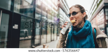 Woman walking down the city and eating sandwich #576356647