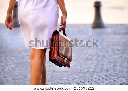 Woman walking home after work with portfolio bag